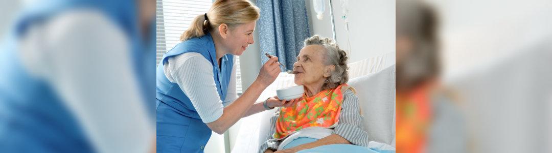 caregiver feeding old woman