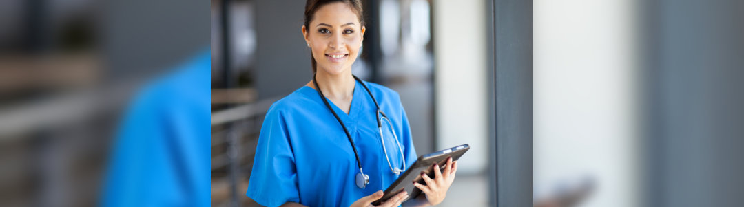 Beautiful young female nurse with tablet device