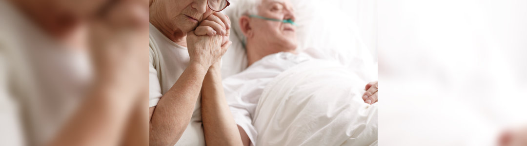 old woman holding handof old man whose lying on bed
