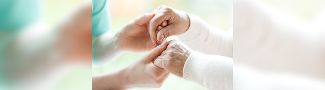 photo with close-up of caregiver and patient holding hands